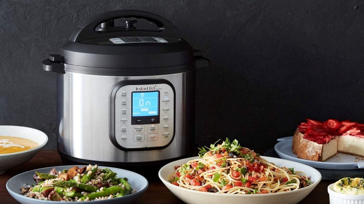 An Instant Pot sitting next to plates of pasta and rice, a bowl of soup, and a cake topped with strawberries.