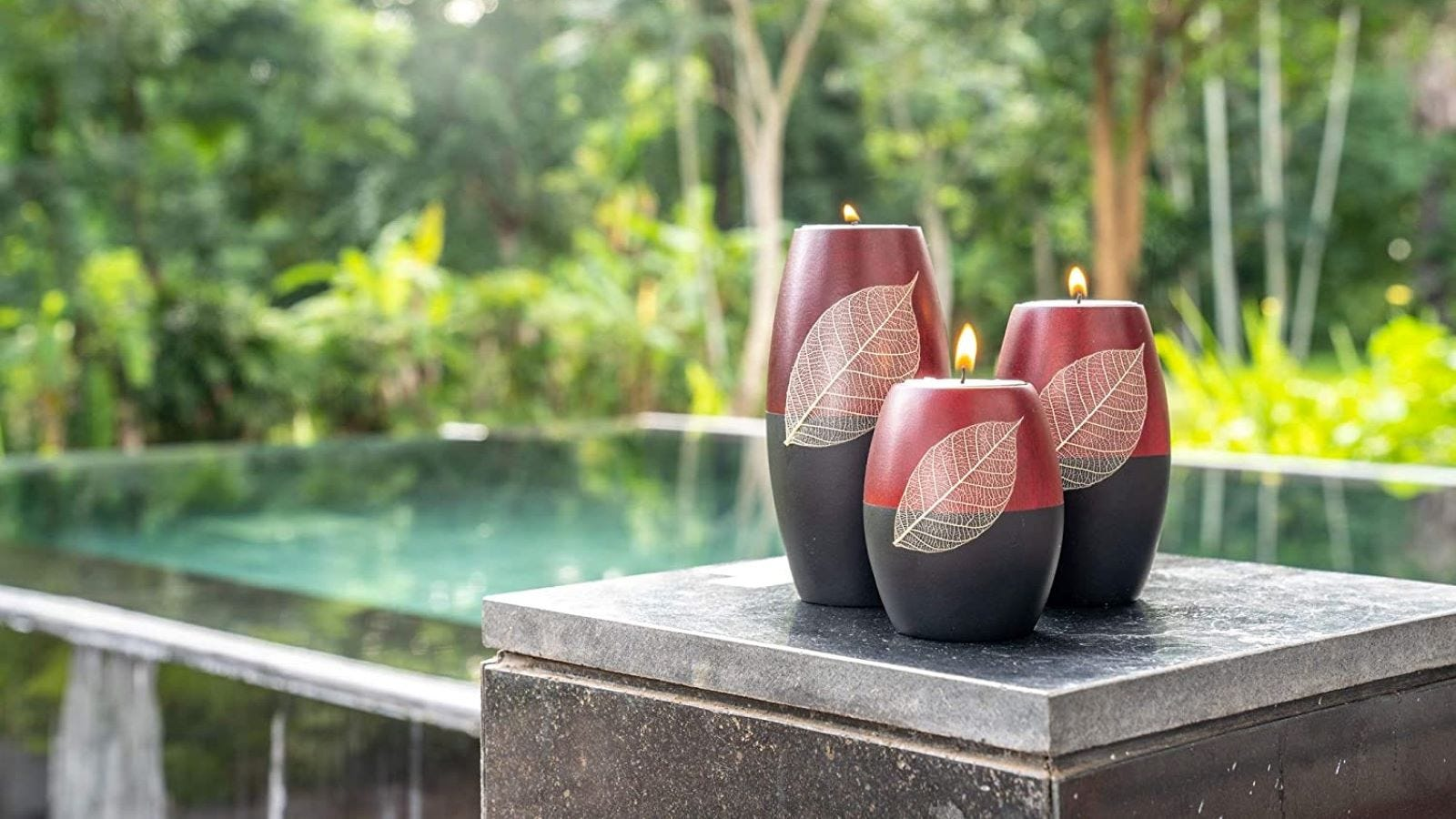 Three red and black wooden candle holders with a leaf patter sitting next to a window facing an infinity pool.