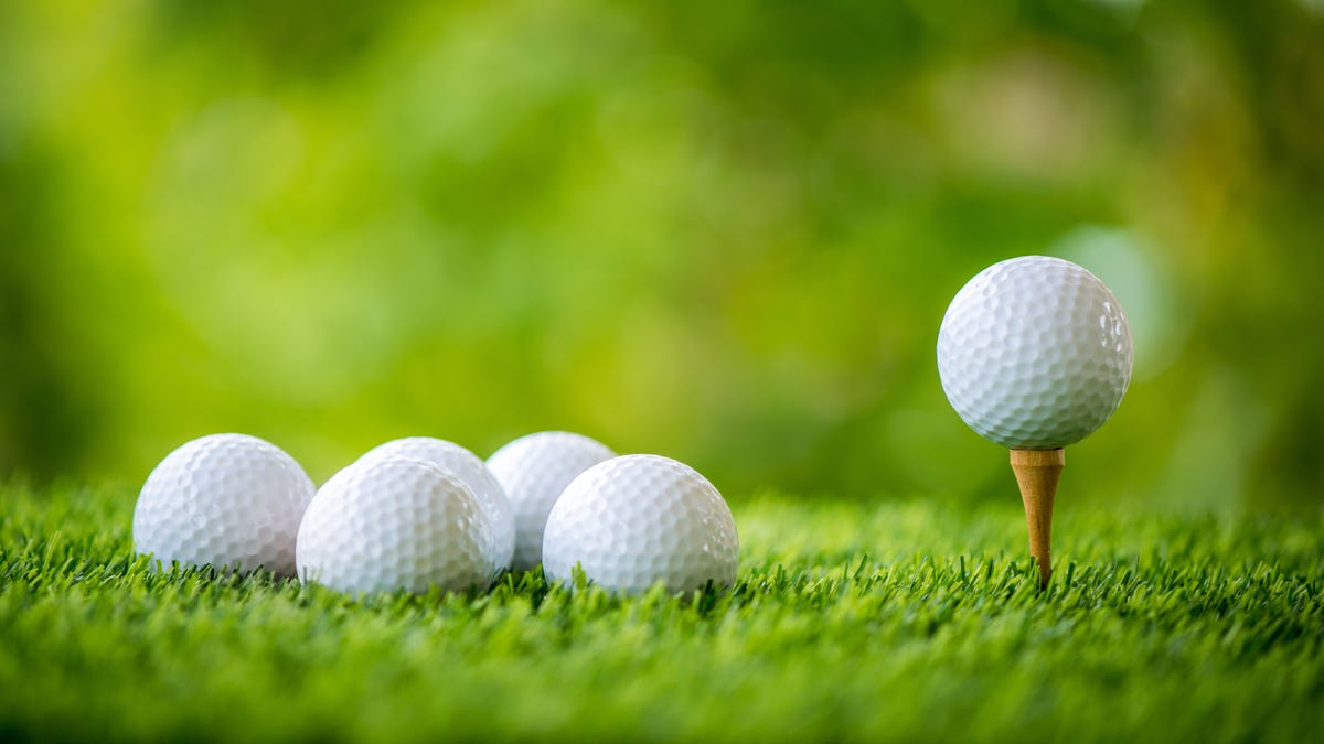 golf balls on a course; one is resting on a tee