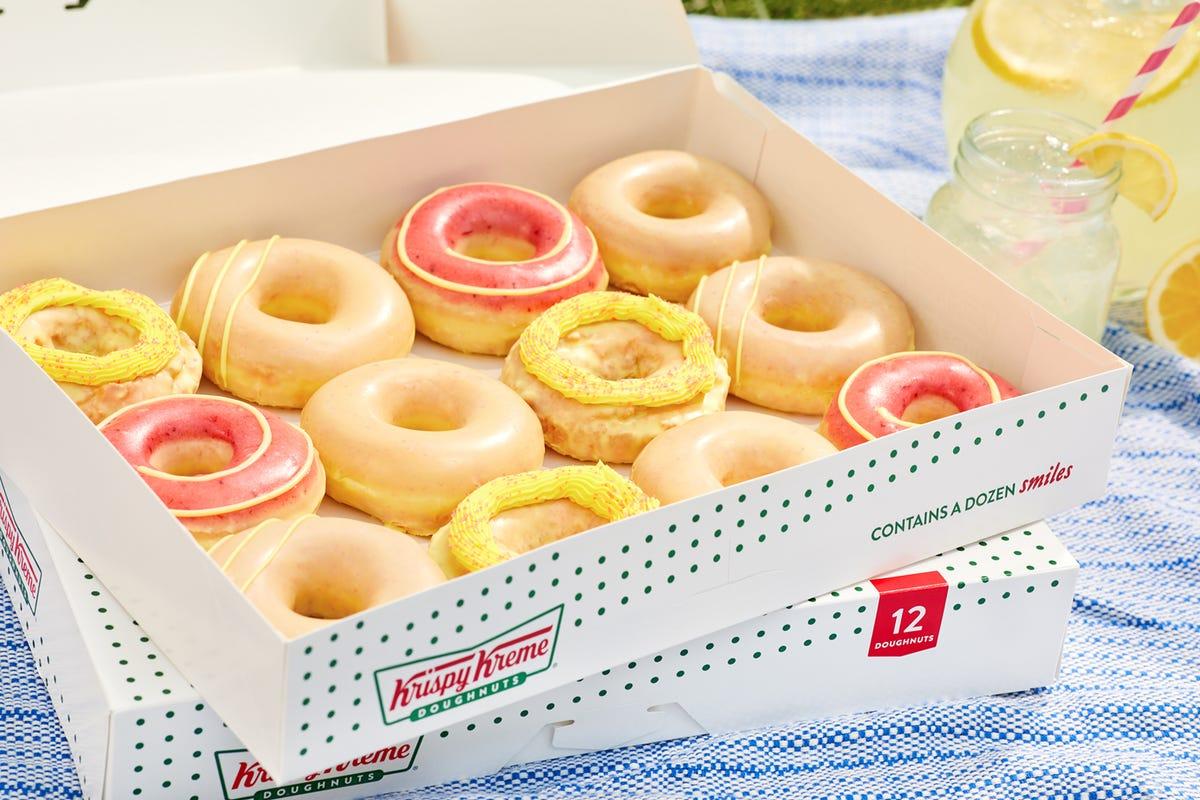 A Krispy Kreme box filled with pink lemonade-flavored doughnuts.