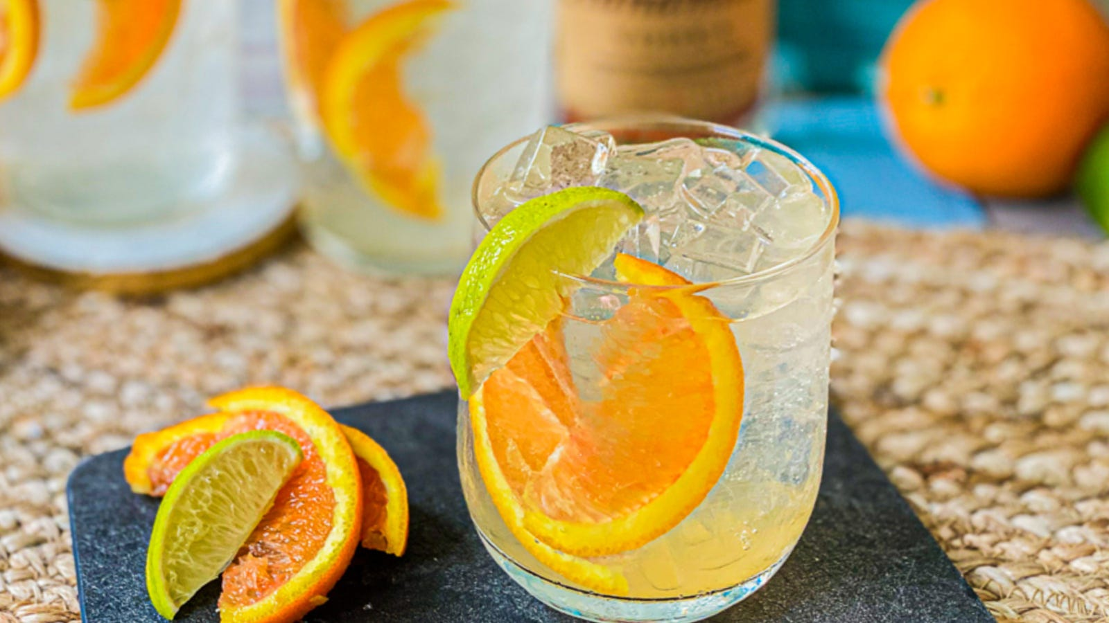A glass of vodka tonic with orange and lime wedges.
