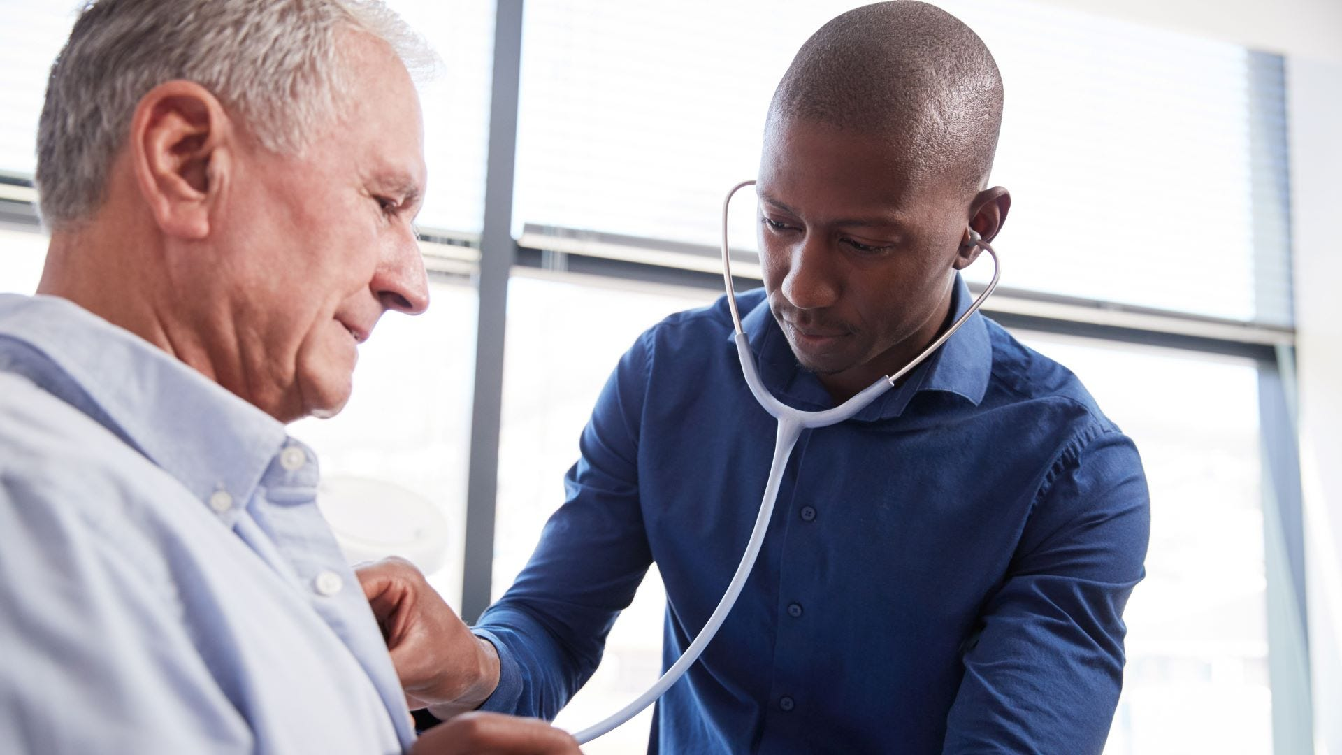 A doctor wearing a stethoscope and listening to a senior male's heartbeat.