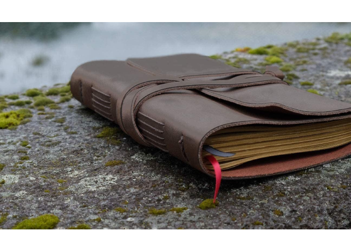 a leather bound journal on top of a rock outside with moss