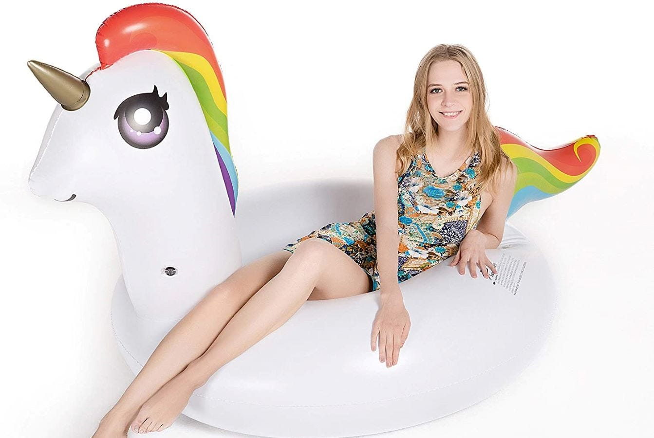 A young girl sitting in the Jasonwell Unicorn Pool Float