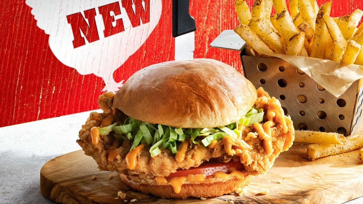 Chili's Chicken Sandwich on a cutting board next to a basket of fries.