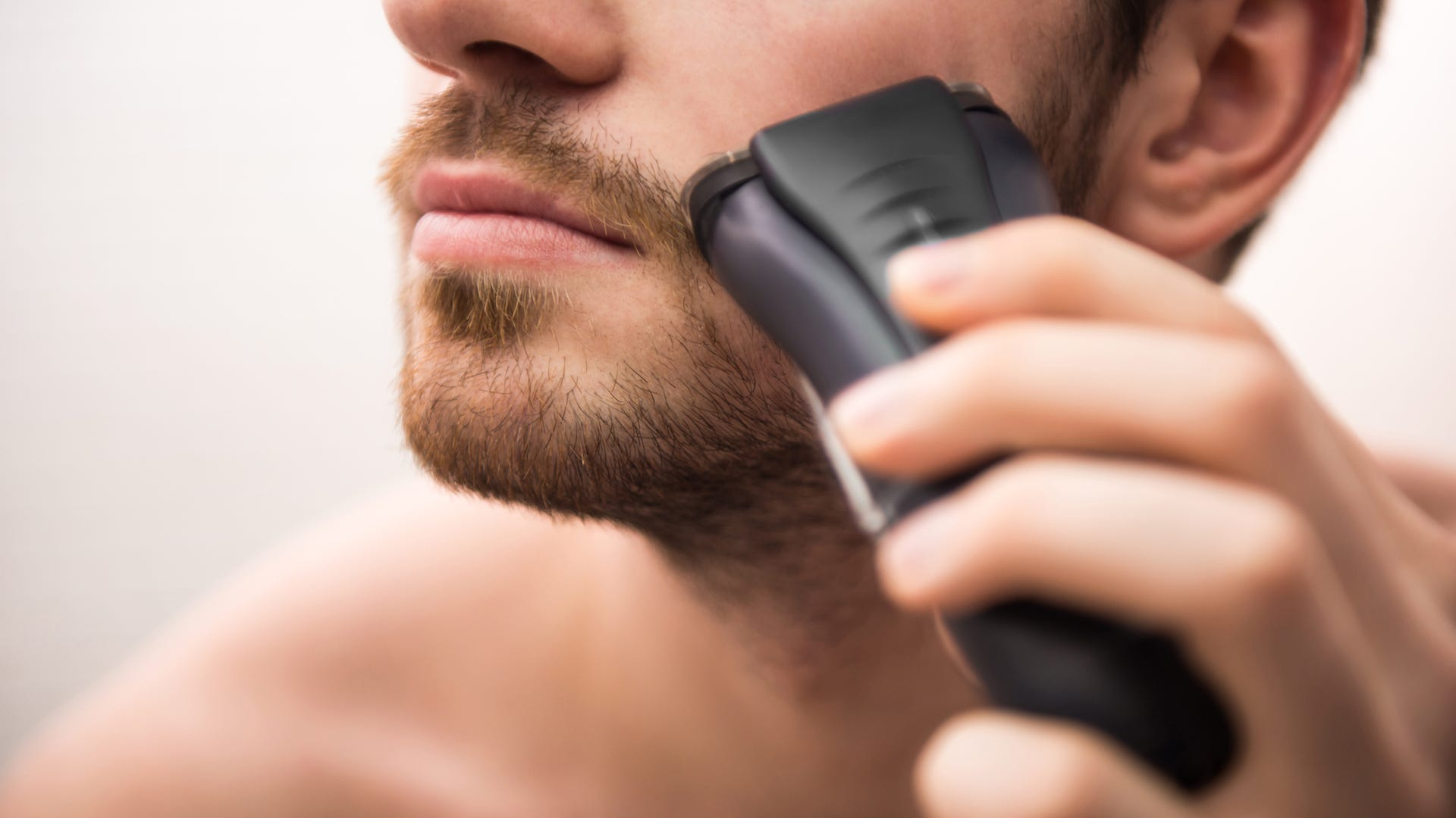 A man uses an electric razor on his beard.