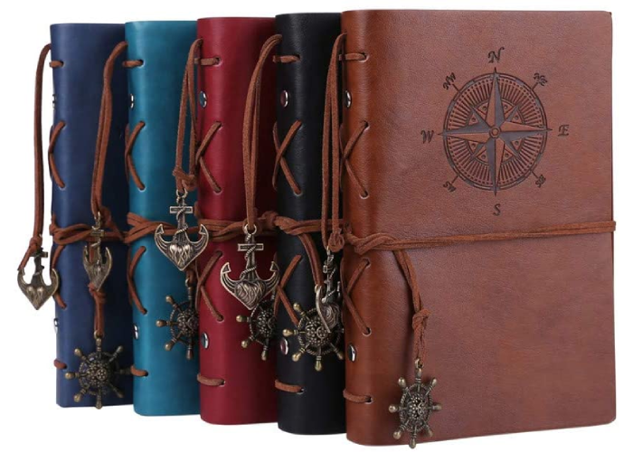 five leather bound journals in navy, blue, red, black and brown with a compass on the front and a bookmark hanging off the side