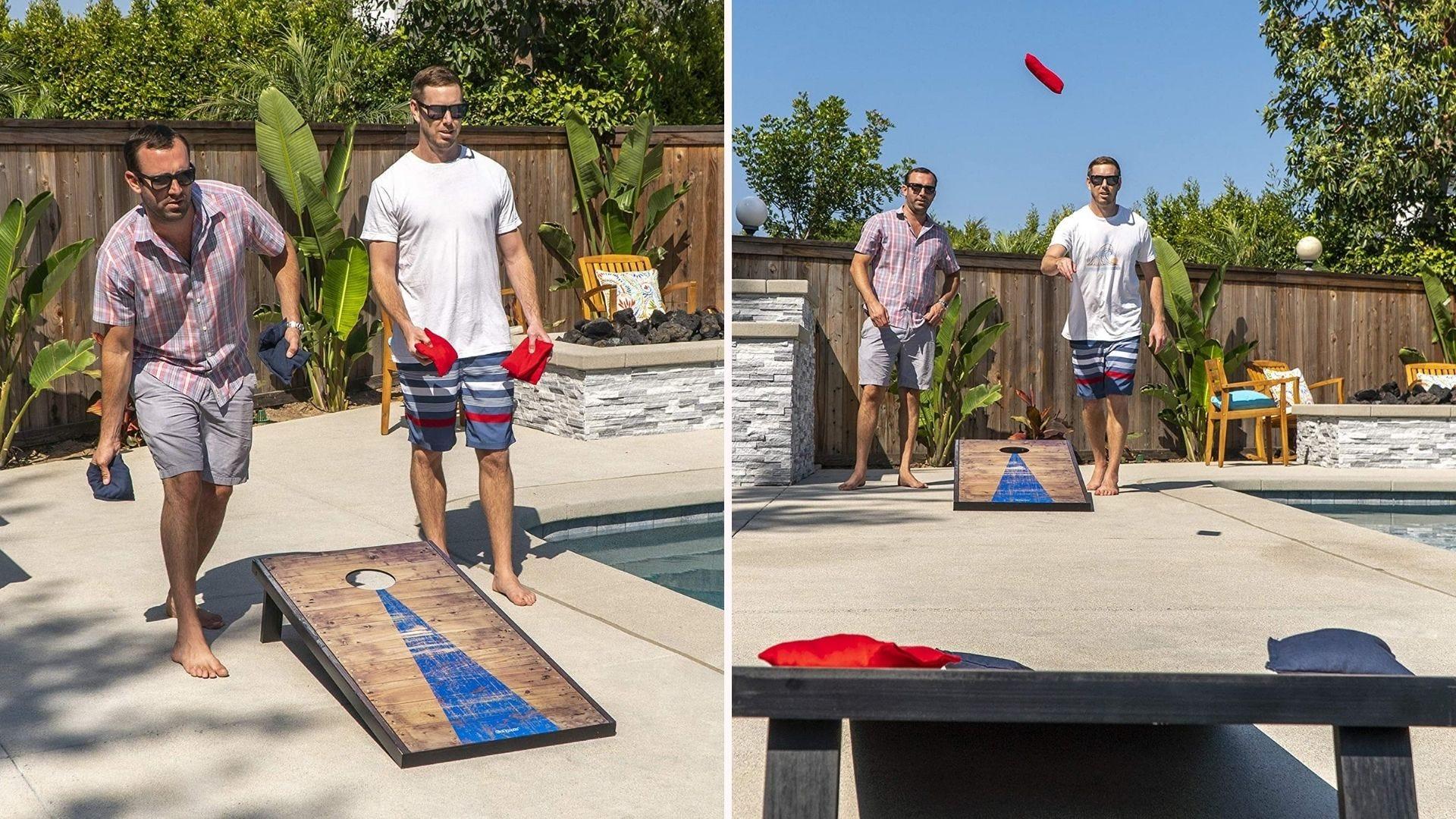 Two men playing cornhole on a pool patio