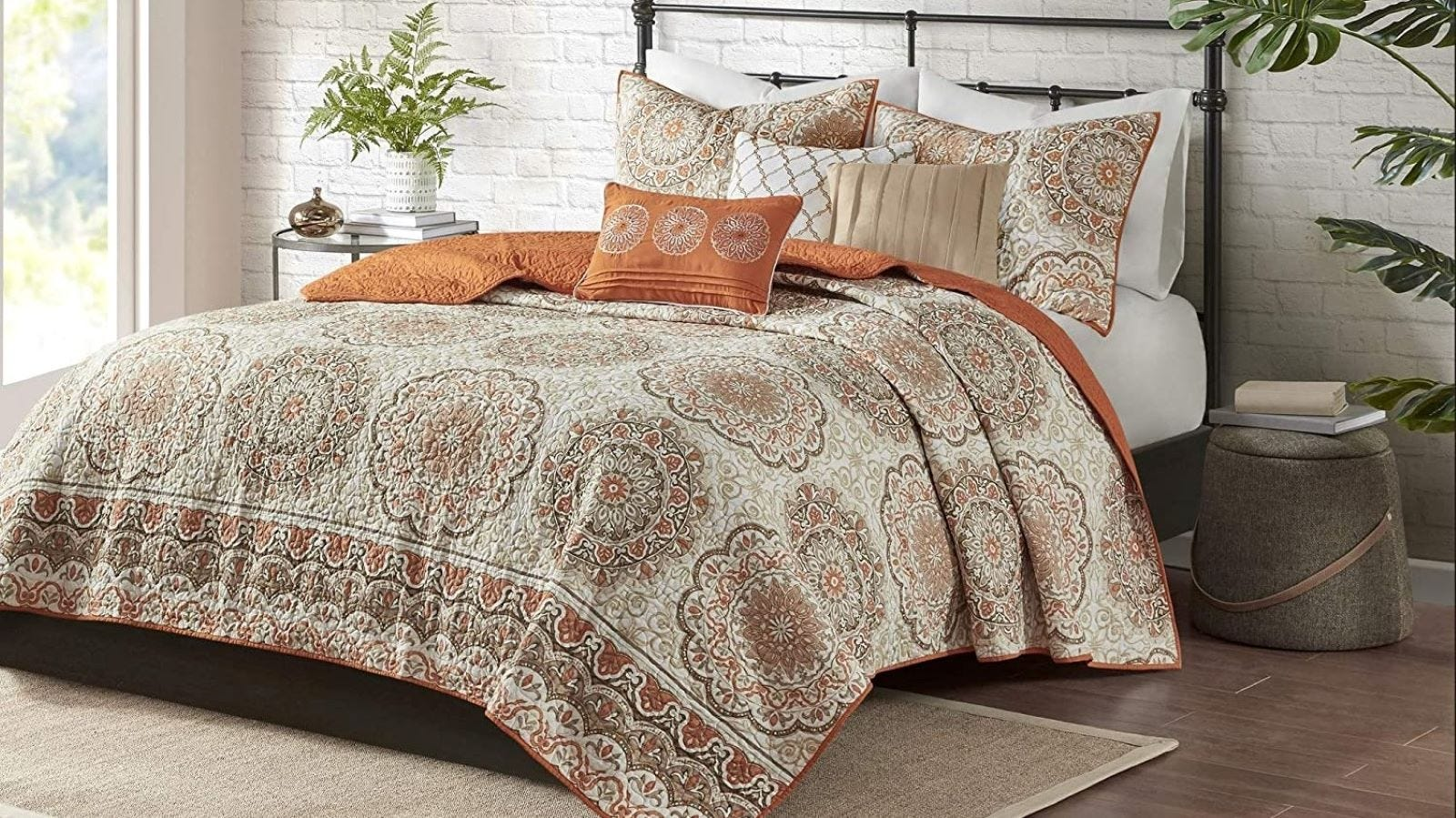 The Madison Park Quilt Set in Tangiers Orange on a metal bed.