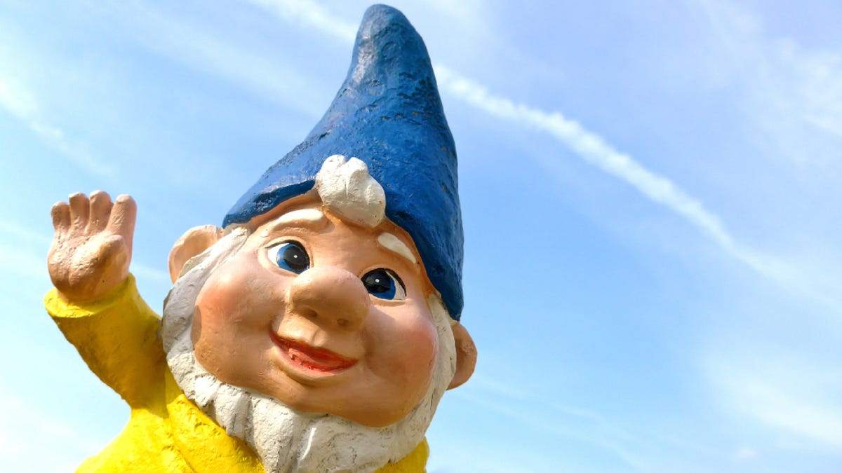 a smiling and waving garden gnome with a blue hat and sky background