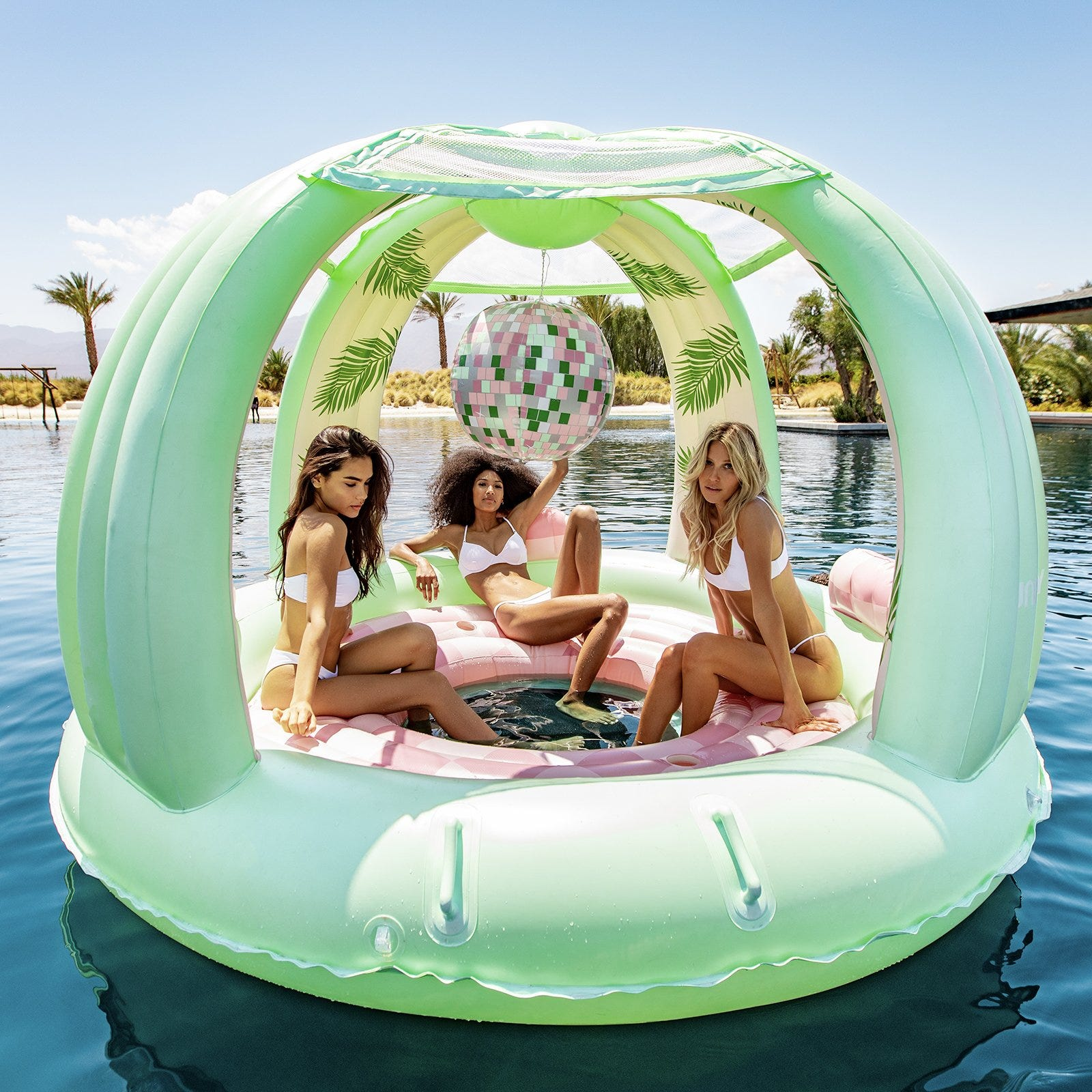 Three women sit in the middle of a floating pink and green dome with an inflatable disco ball hanging from the center.
