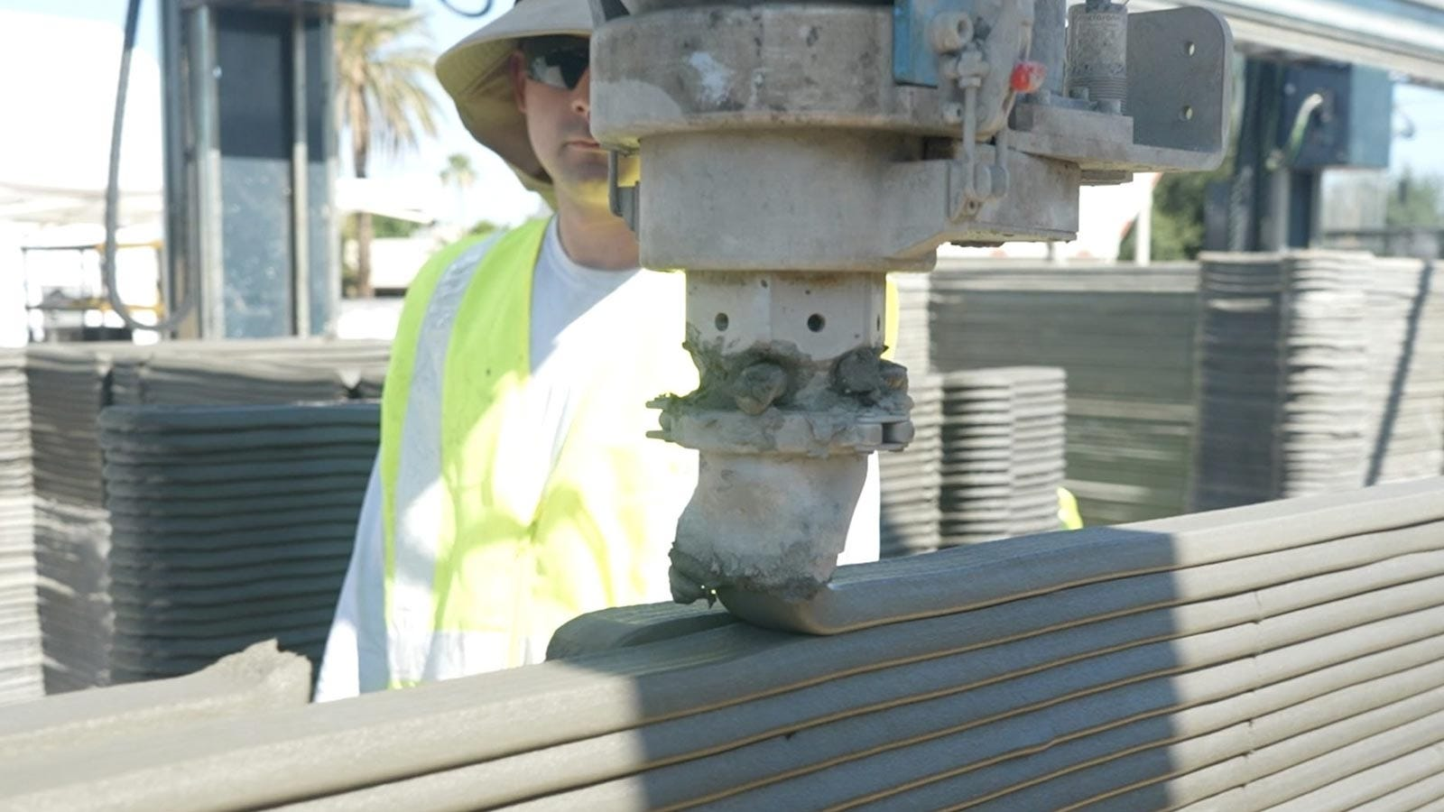 A construction worker watches a concrete 3D printer lay down a wide band of concrete.