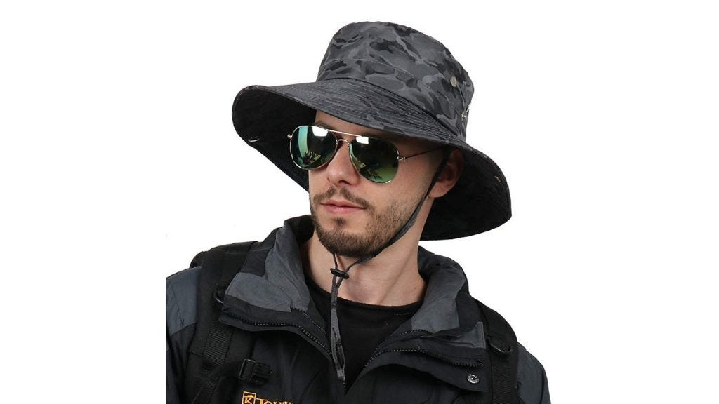 a man wearing a camo fabric sun hat with a chin strap and aviator sunglasses
