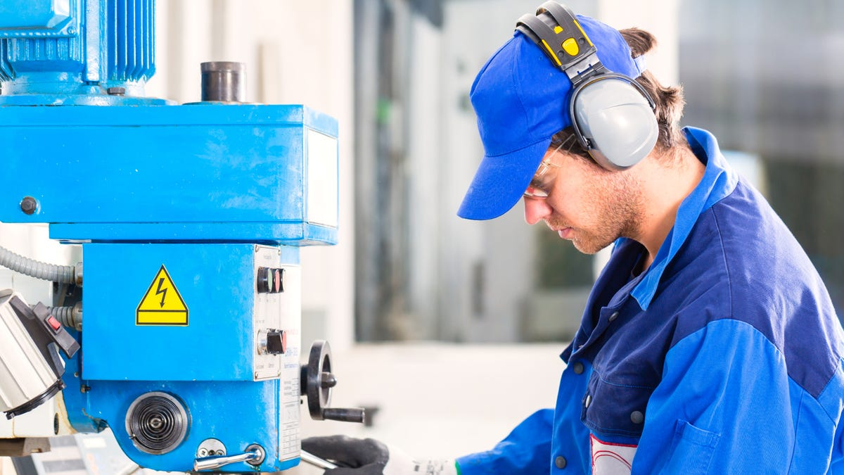 Craftsman wearing a blue shirt and ear protection while drilling metal with drill in a workshop.