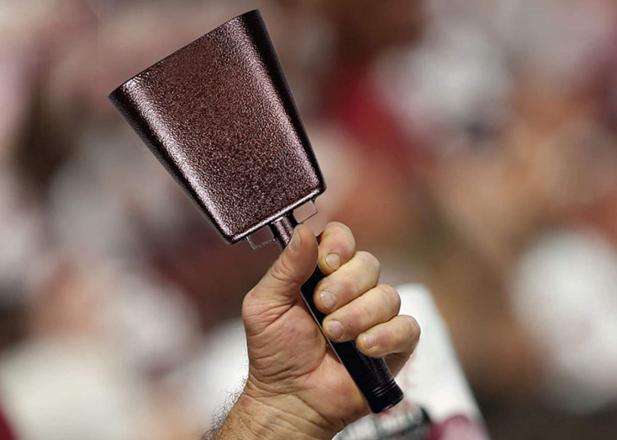 a hand holding a cowbell up at a sports game in the crowd