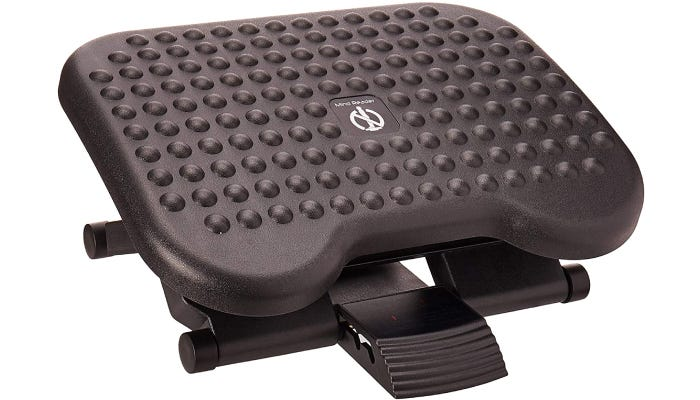 An angled footrest with raised bumps on the surface