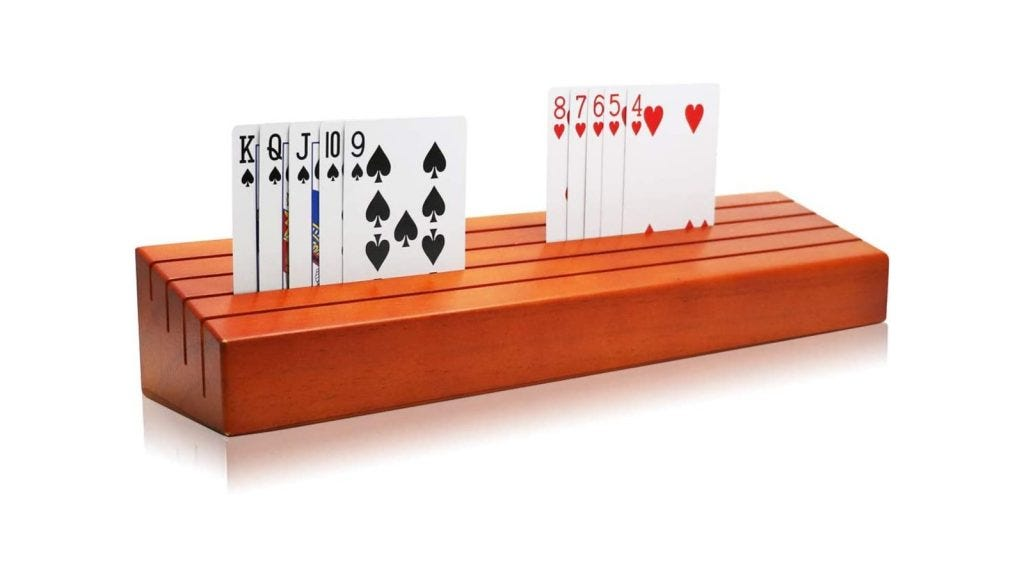 A wooden playing card holder that features four ascending slots