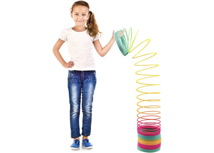 a girl holding a large-size, multicolored spring toy to her shoulder height.