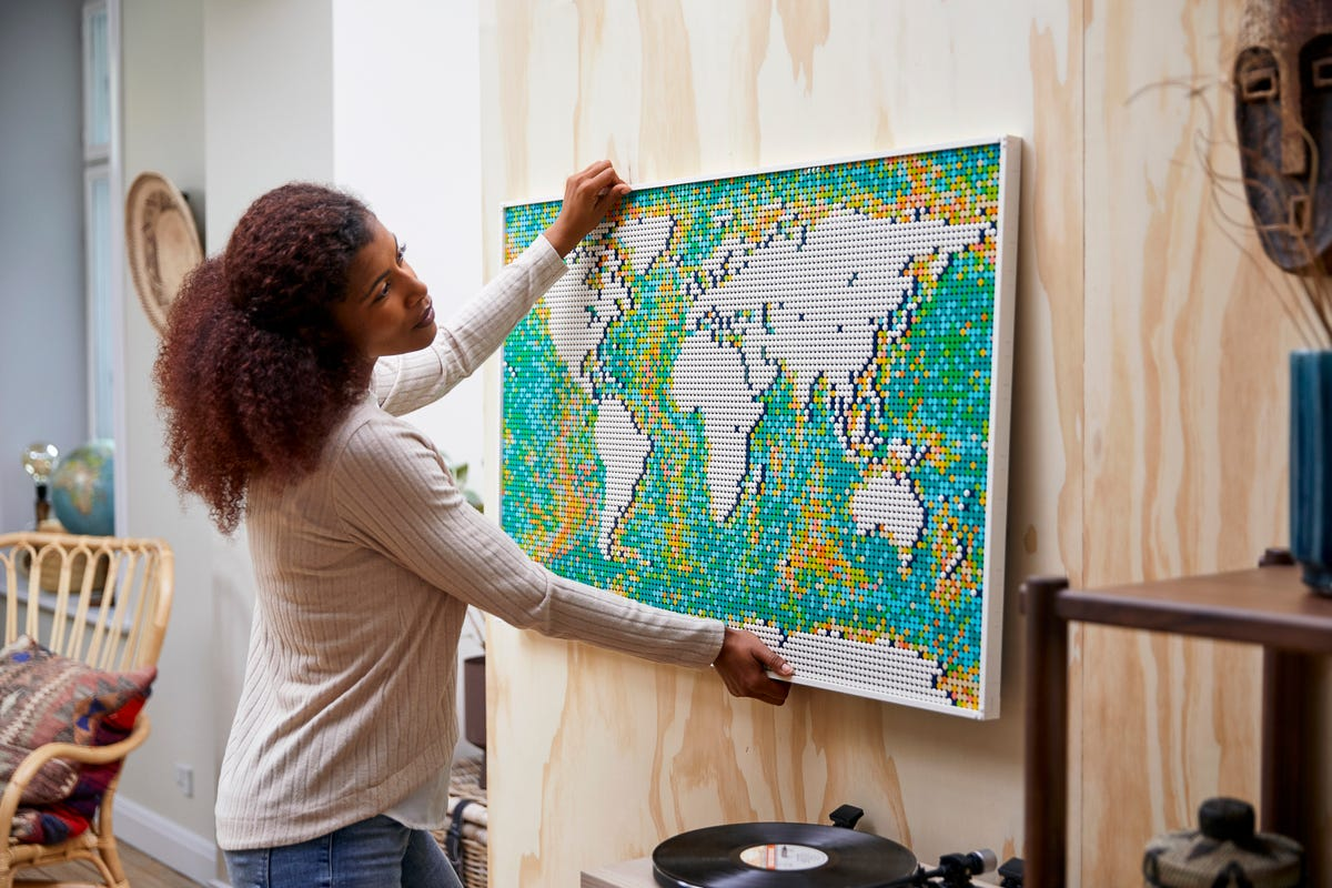 A woman hangs an assembled map of the world made from LEGOs