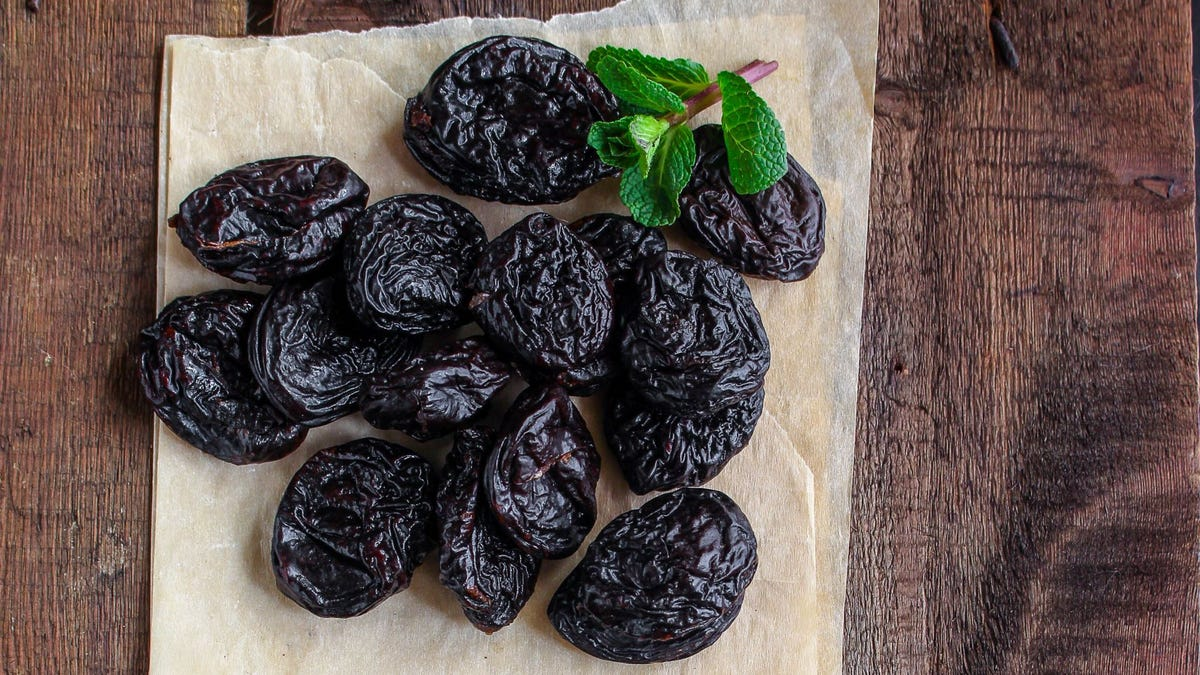A pile of prunes on parchment paper.