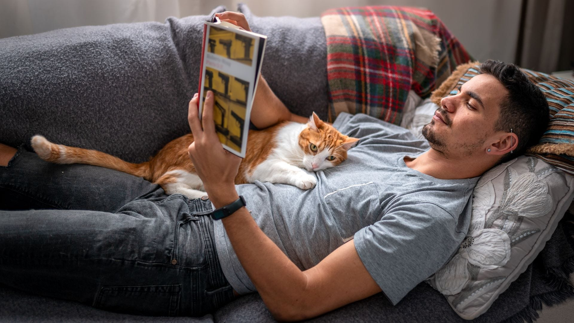 A man reading on a couch with a cat on his chest.