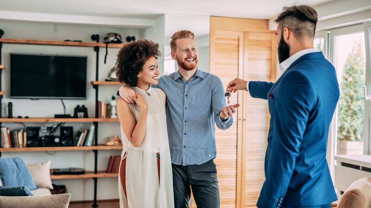A realtor handing a young couple the keys to their new home.