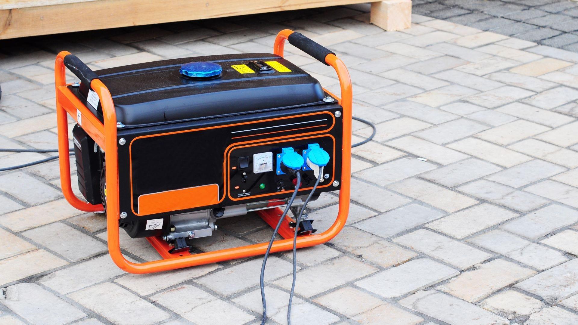 An orange generator sitting on a patio.
