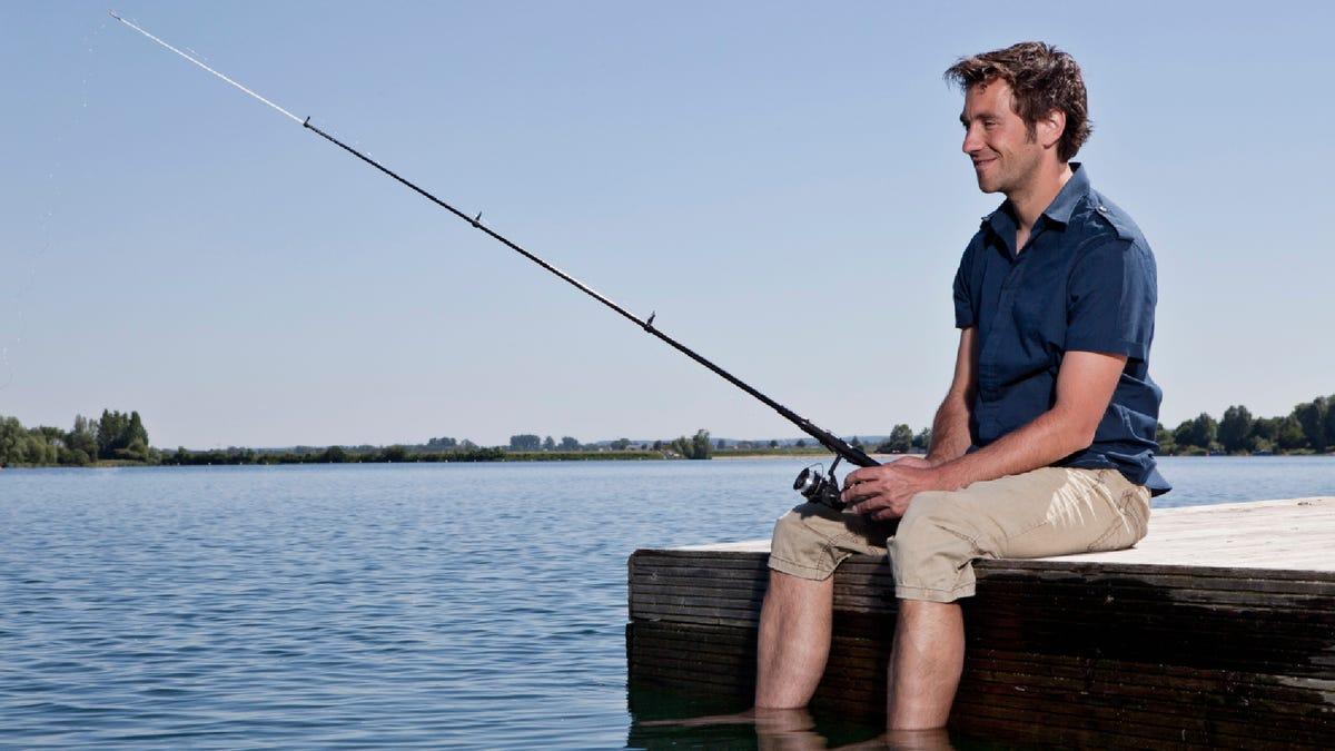 a man sitting on a dock fishing