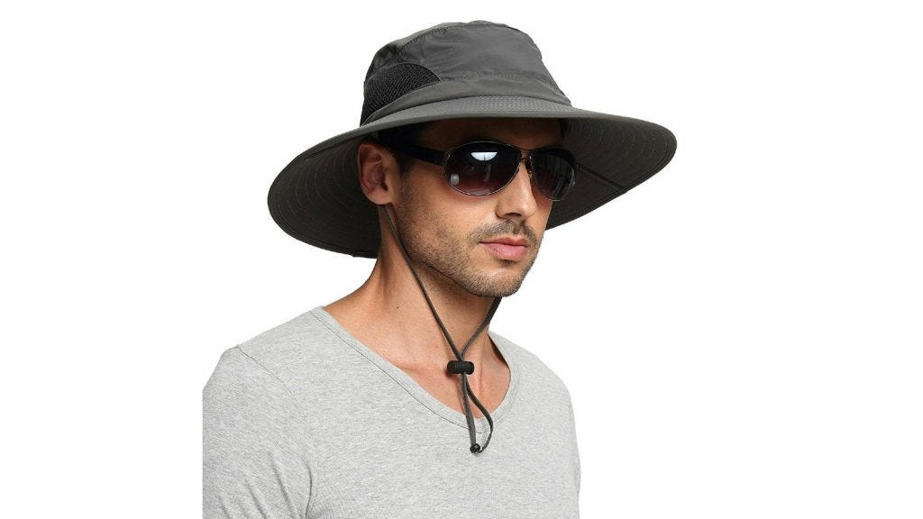 a man wearing a gray fabric sun hat with a strap and sunglasses