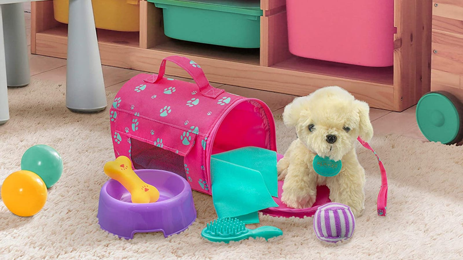 A light-colored dog stuffed animal wears a pink leash and stands next to its matching carrier and accessories.