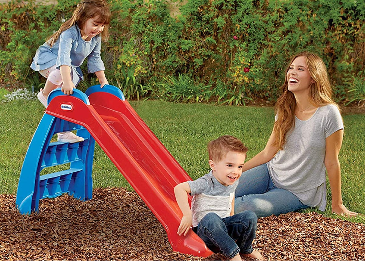 two toddlers sliding down a slide outside while mom watches with a smile