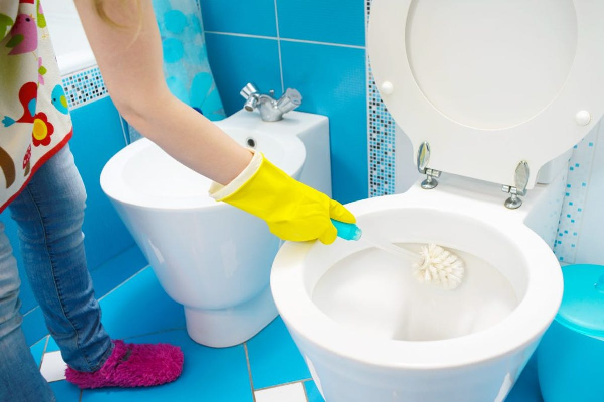 A woman cleans a bathroom toilet with a scrub brush.