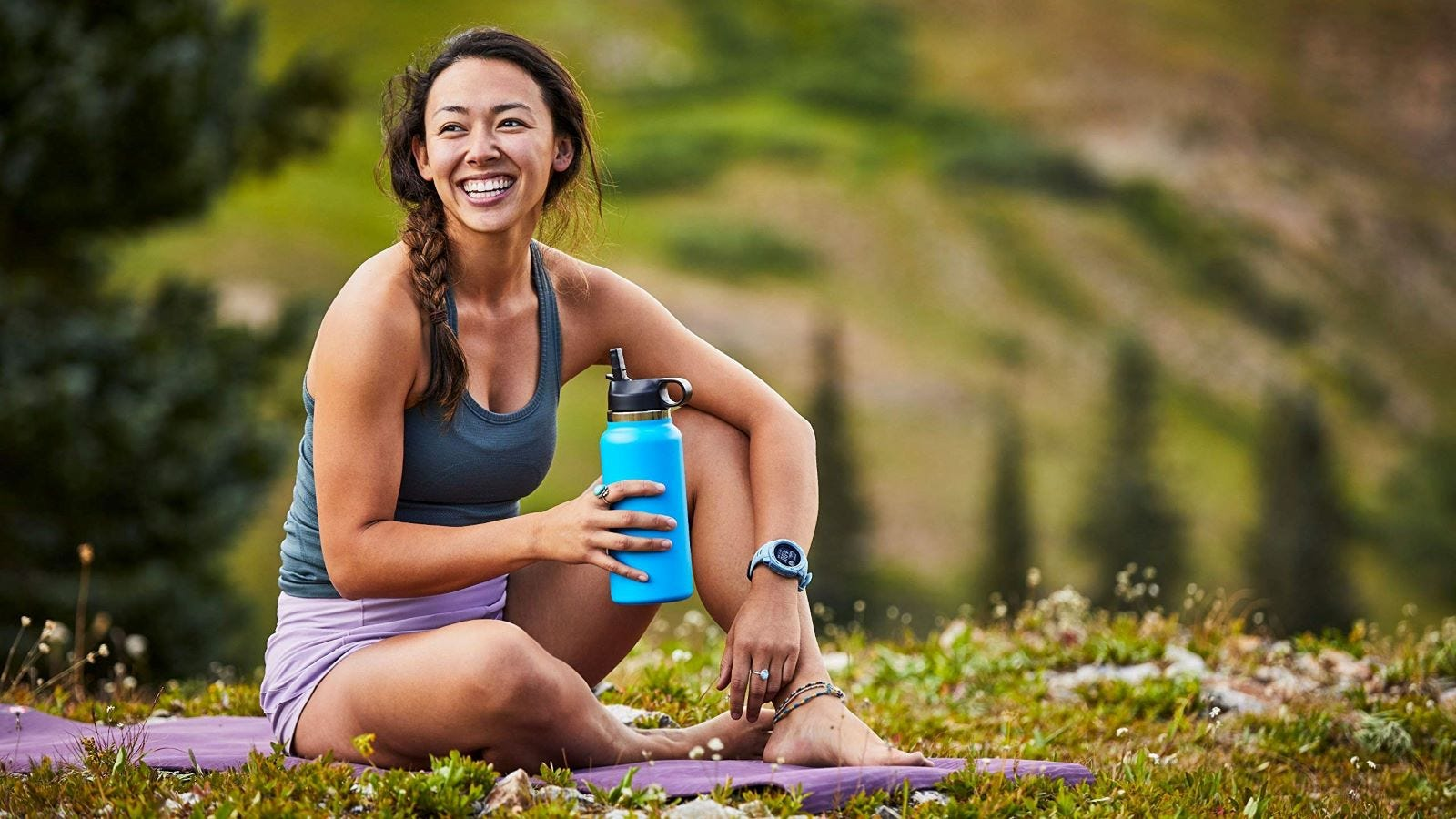 A woman sitting on a blanket at a park holding a Hydro Flask Water Bottle.