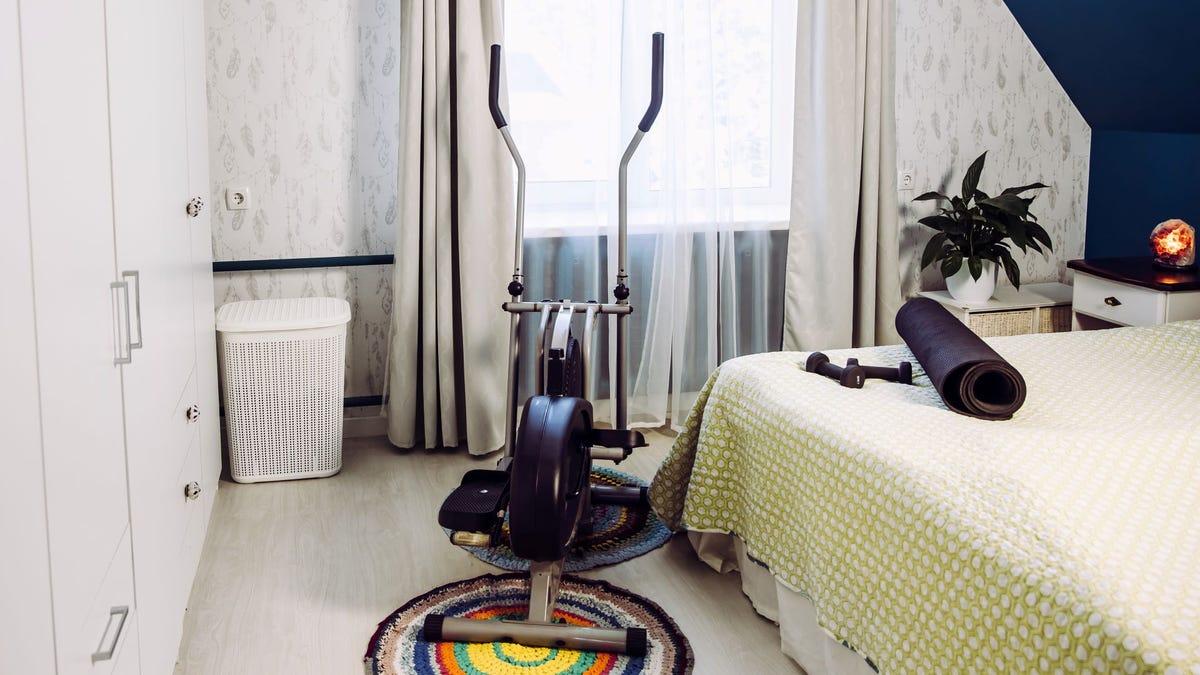 An elliptical machine in a bedroom.
