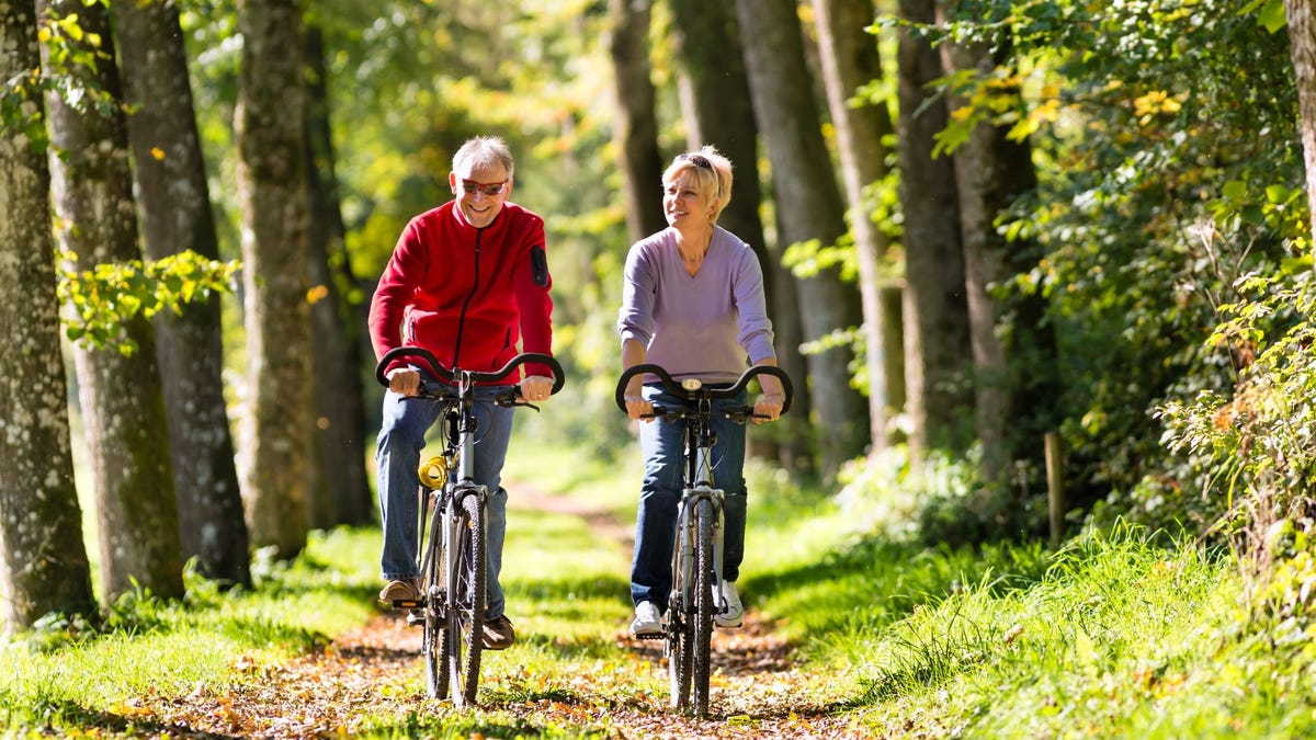 A senior man and woman bicycling on a forest trail.