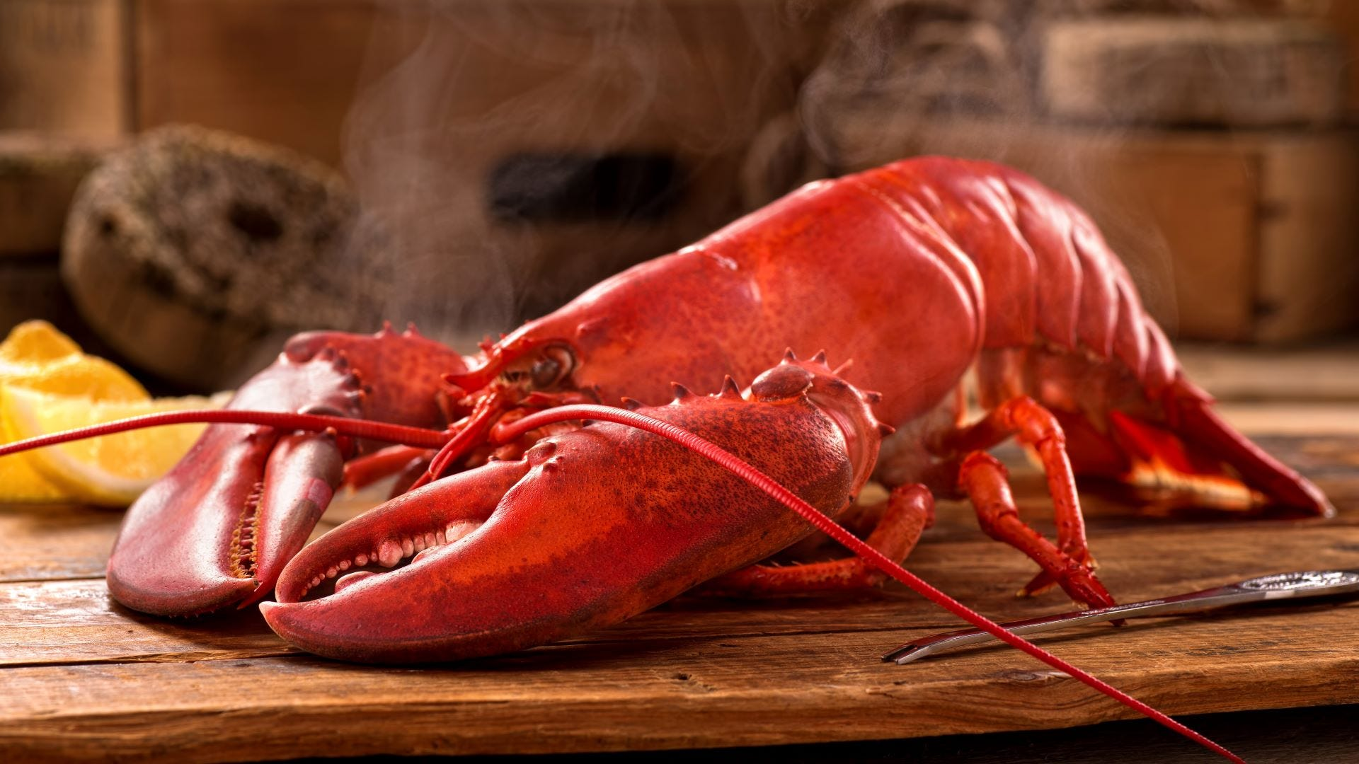 A lobster on a wooden table with steam coming off it.