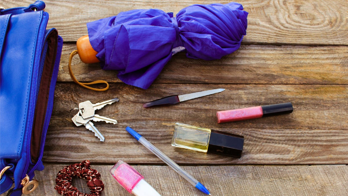 a mini umbrella, keys, lip gloss, and other small items on a wooden table next to an open purse