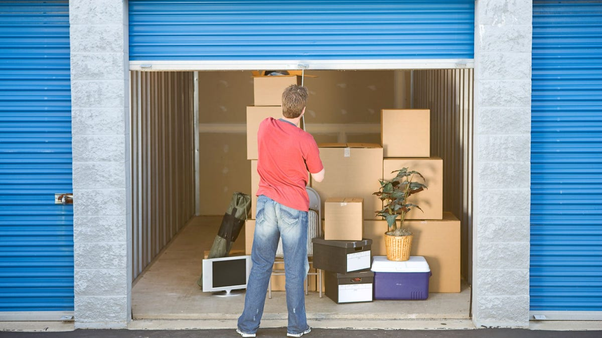 A man closing the door on a storage unit.