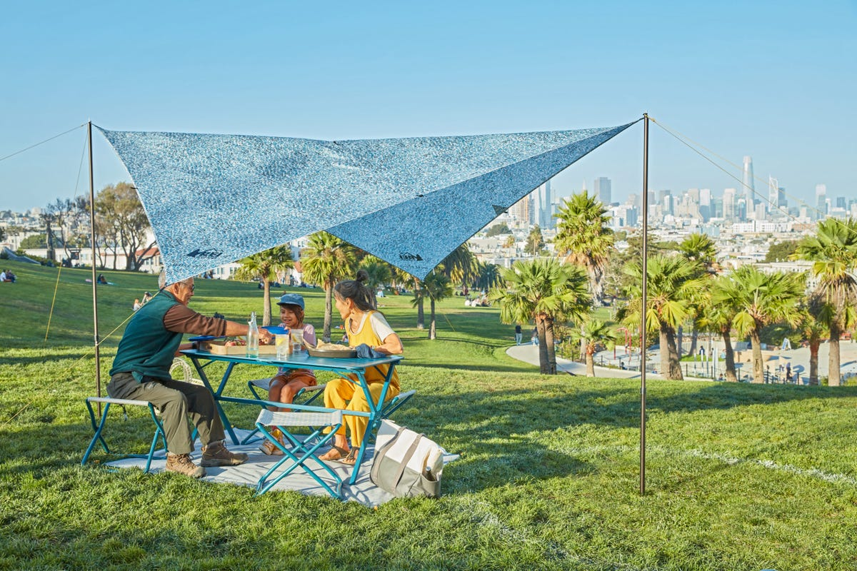 Grandparents and their grandchild sit at a blue picnic table under a blue patterned tent.