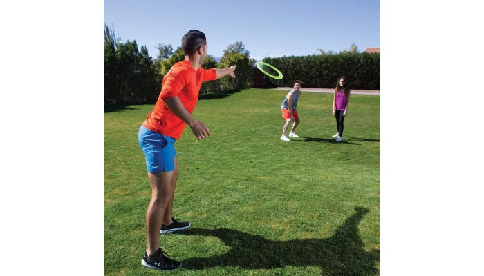 Three people playing with green frisbee in a grassy park