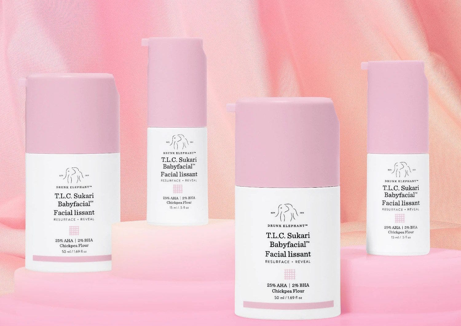 Four white bottles with pink caps on a pink background