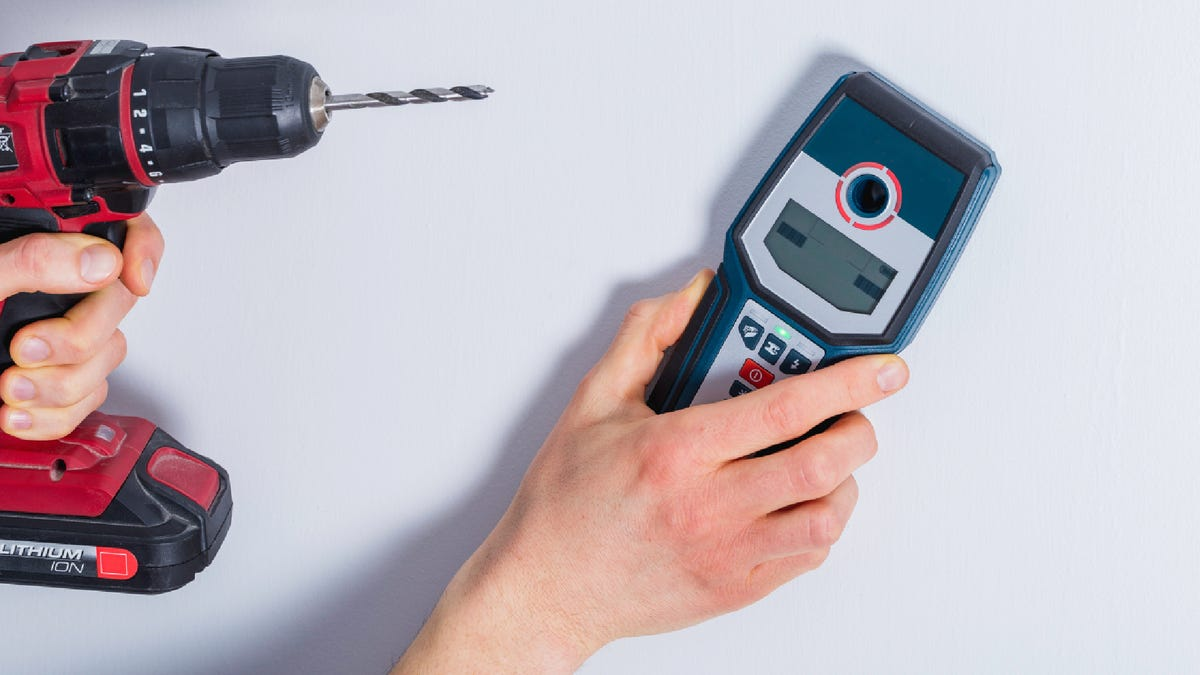 man using a stud finder on a wall and holding a drill in his other hand