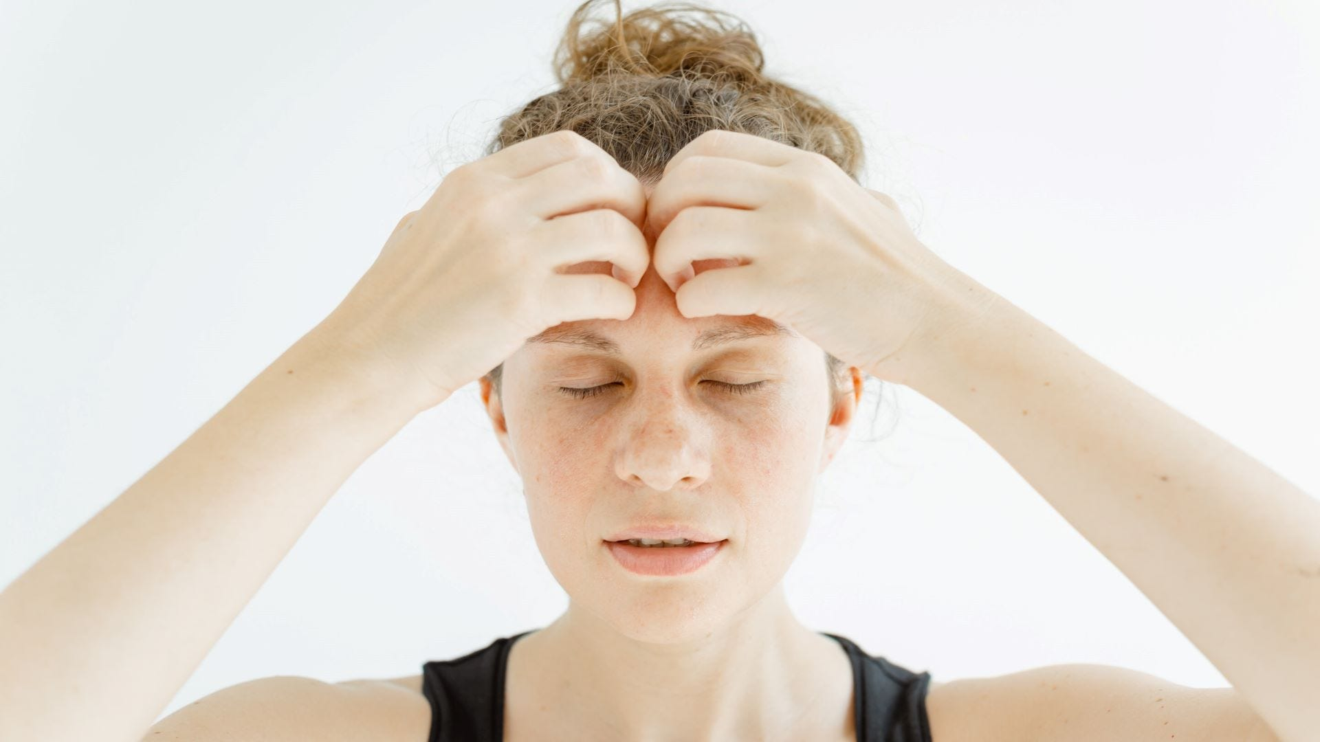 A woman doing the forehead face yoga move.
