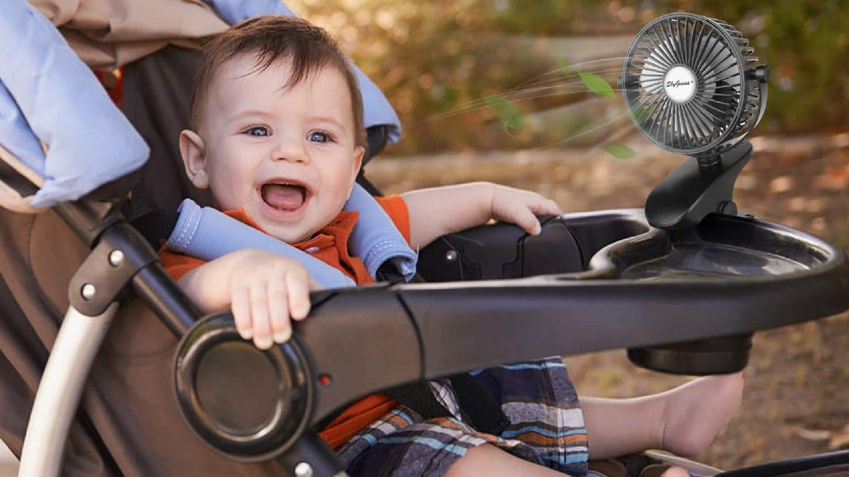 baby smiles in his stroller with a stroller fan blowing air on him