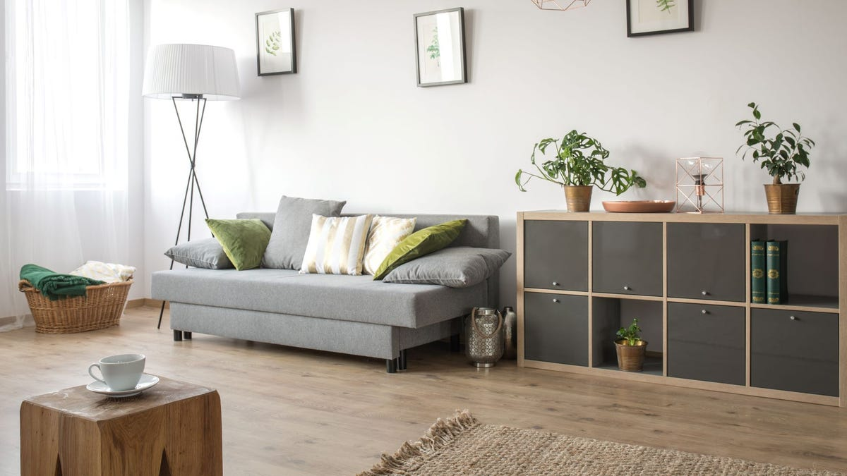 A neutral living room with a soft gray sofa and light wooden accents.