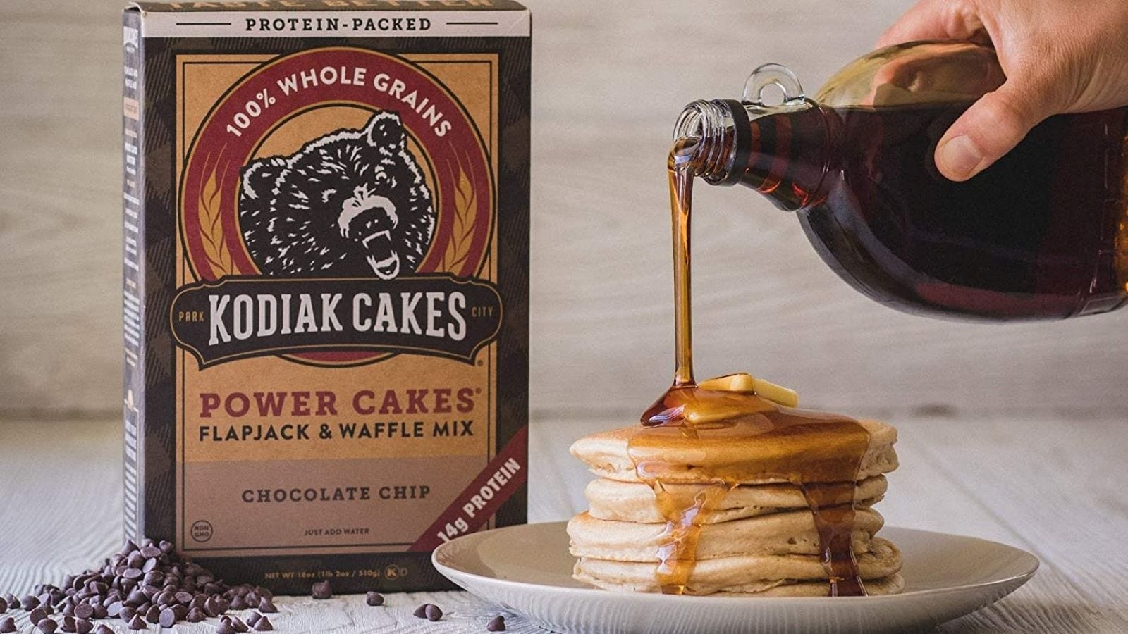 A pack of Kodiak Cakes Flapjack and Waffle Mix next to a stack of pancakes and someone pouring syrup on them.