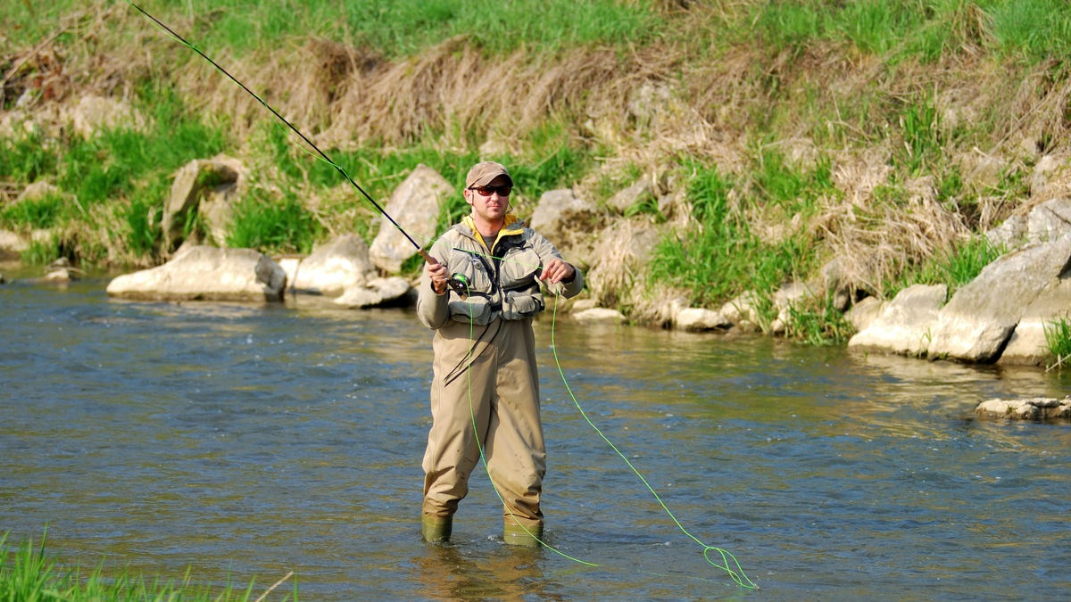 A fisherman wearing beige waders angling on a river.