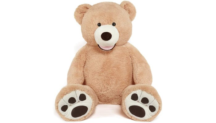 A light brown, 51-inch stuffed teddy bear sits in an upright position, showcasing its detailed paw-prints.
