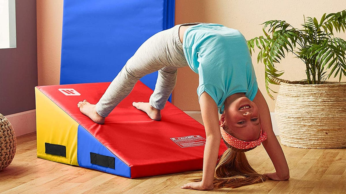 A young girl doing a back handspring on a colorful gymnastics wedge.
