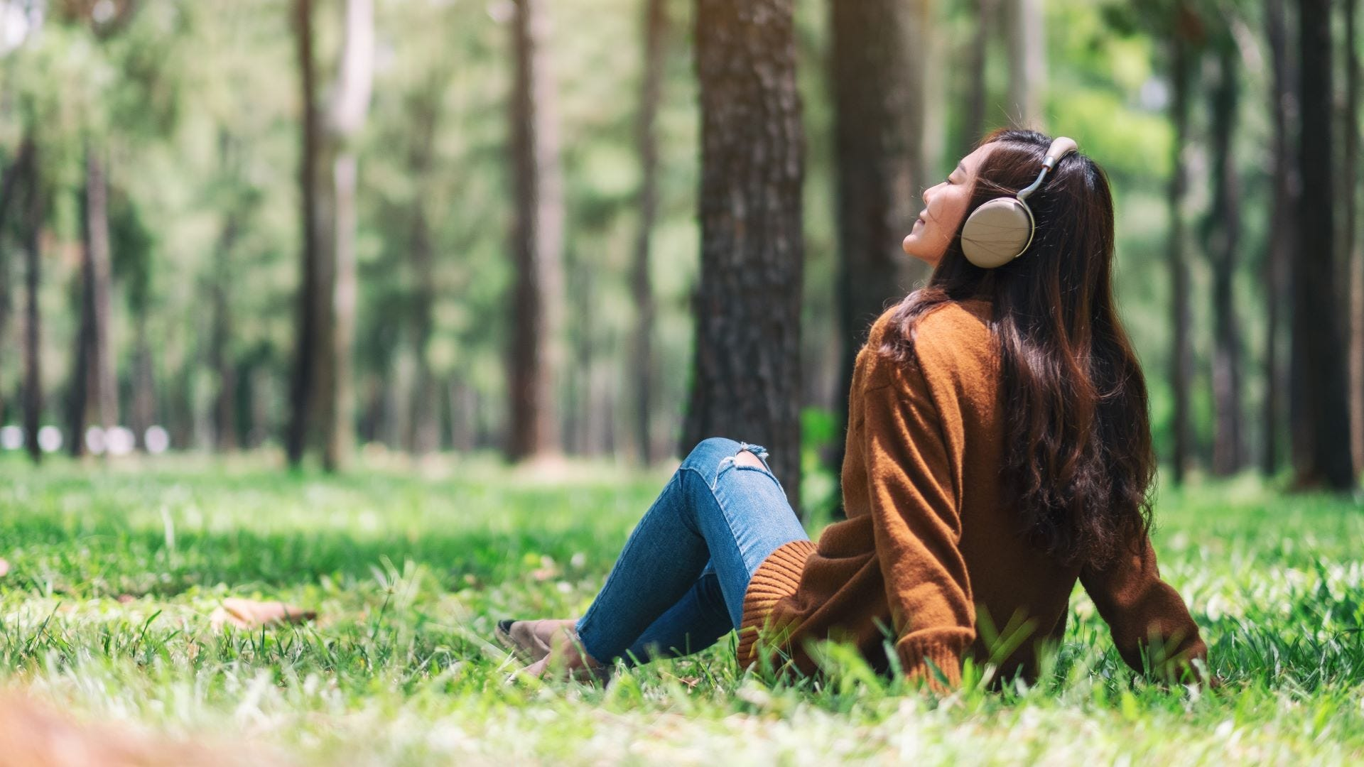 A young woman sitting on the grass in the park and listening to music on headphones.